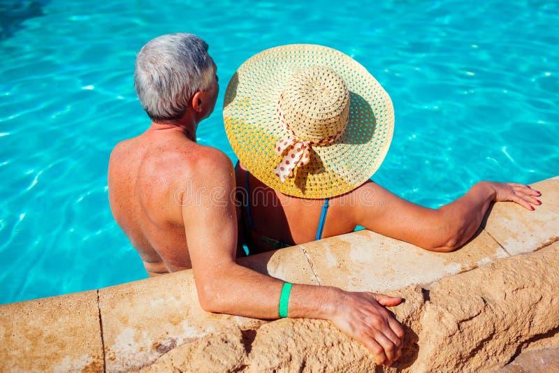 Pares mayores que se relajan en piscina Gente que disfruta de vacaciones de verano Todo inclusivo imagen de archivo libre de regalías