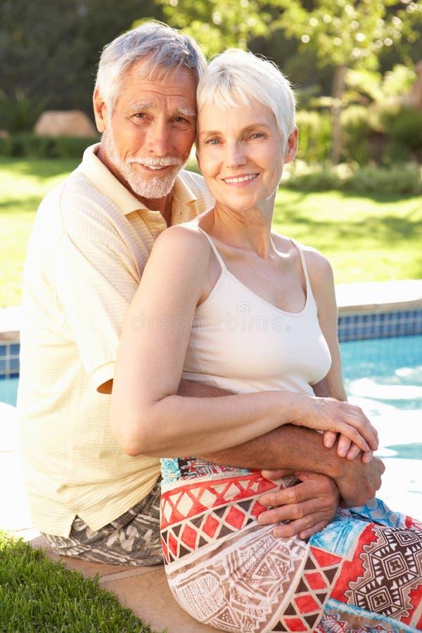 Pares mayores que se relajan por el jardín de Pool In fotos de archivo libres de regalías