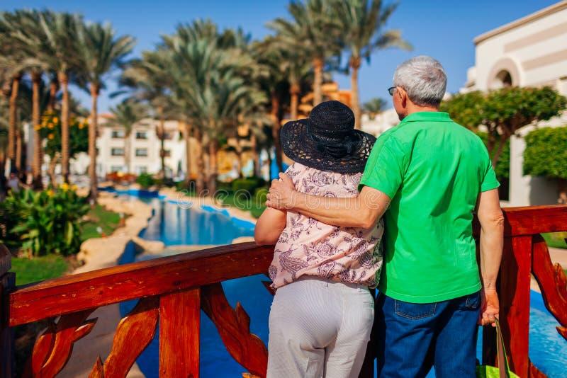 Pares mayores que se relajan por la piscina en territorio del hotel Gente que disfruta de vacaciones Día del `s de la tarjeta del imagenes de archivo