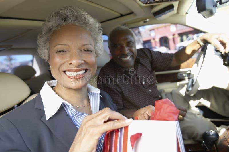 Pares mayores que se sientan en coche, en viaje de las compras imagenes de archivo