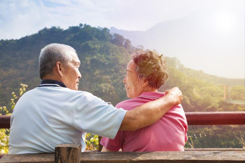 Pares mayores que se sientan en el banco en parque de naturaleza foto de archivo