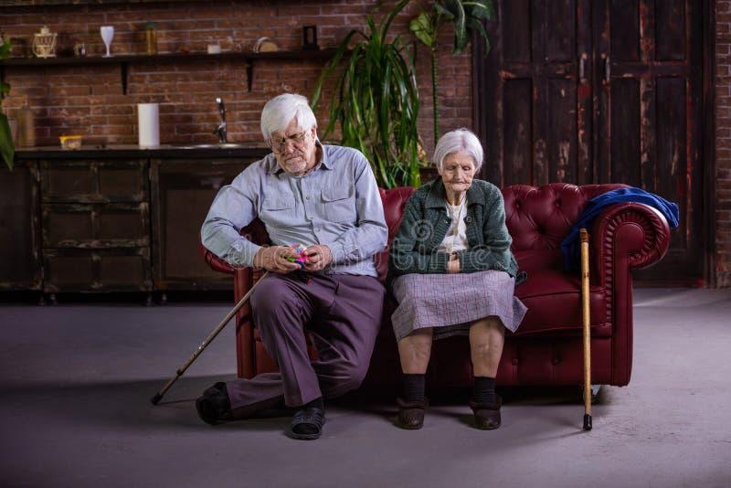 Pares mayores que se sientan en el sofá imagen de archivo libre de regalías