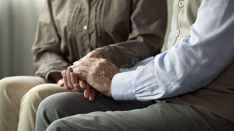 Pares mayores que se sientan en el sofá, llevando a cabo las manos, entendiendo en matrimonio largo fotografía de archivo