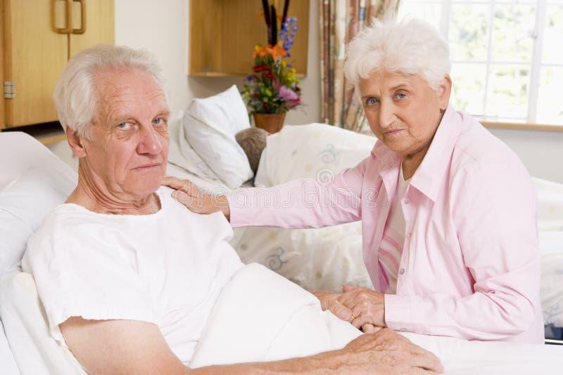 Pares mayores que se sientan en hospital foto de archivo