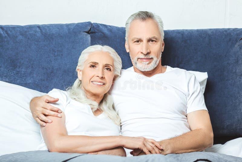Pares mayores que se sientan en la cama imagen de archivo