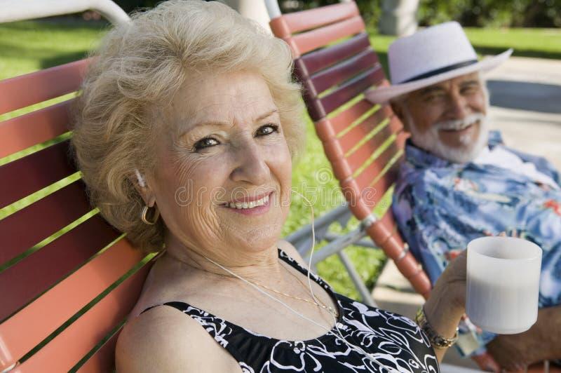 Pares mayores que se sientan en la mujer de las sillas de jardín que escucha los auriculares y que sostiene el retrato de la taza. imagen de archivo