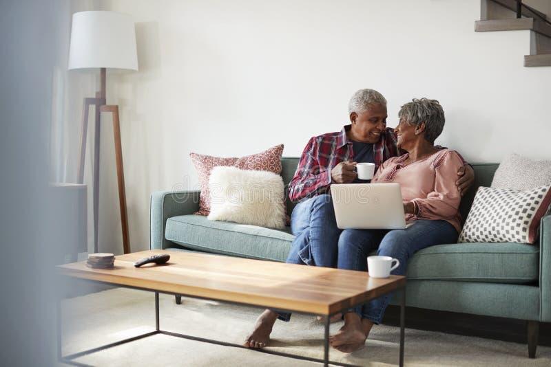 Pares mayores que se sientan en Sofa At Home Using Laptop para hacer compras en línea fotografía de archivo libre de regalías