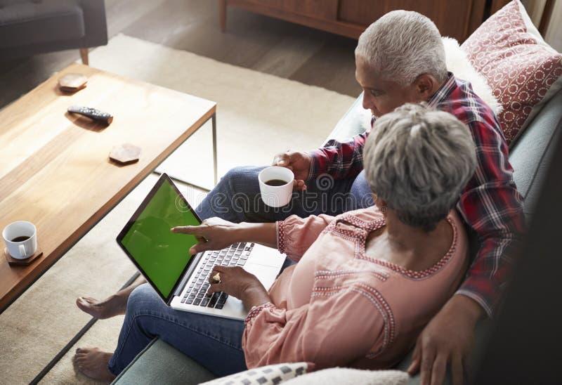 Pares mayores que se sientan en Sofa At Home Using Laptop para hacer compras en línea fotos de archivo