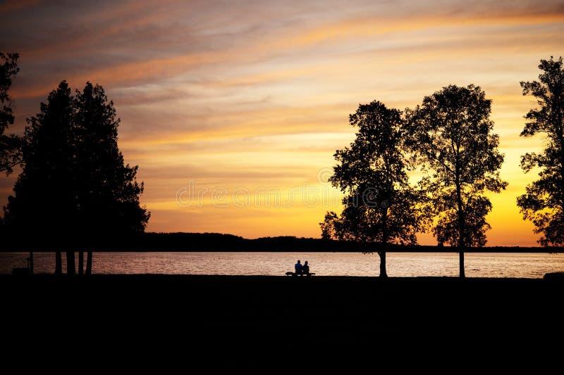 Pares mayores que se sientan en un banco por el lago en el sunse fotografía de archivo libre de regalías