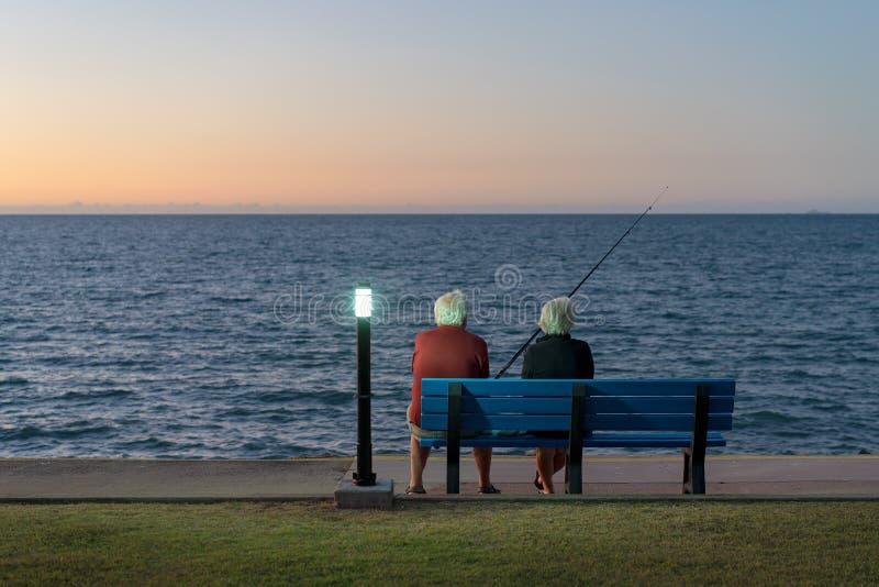 Pares mayores que se sientan en una pesca del banco foto de archivo libre de regalías