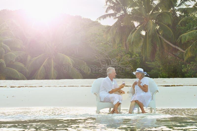 pares mayores que se sientan en una playa fotos de archivo