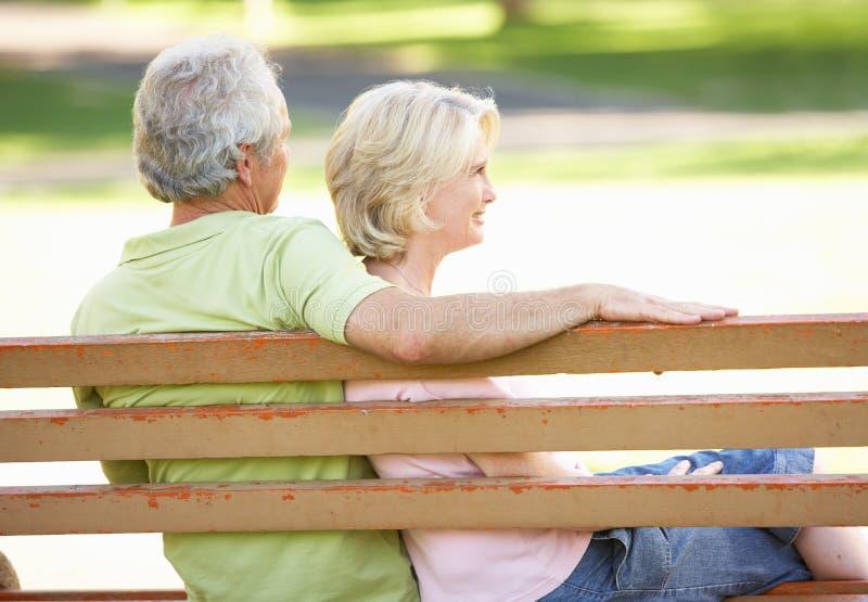 Pares mayores que se sientan junto en banco de parque fotografía de archivo libre de regalías