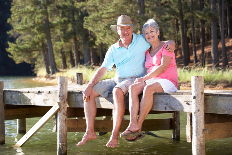 Pares mayores que se sientan por el lago imagen de archivo libre de regalías