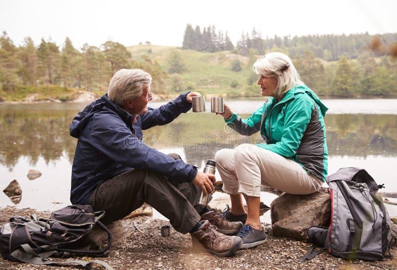 Pares mayores que se sientan por un café de consumición del lago durante la acampada que hace una tostada con sus tazas, distrito fotos de archivo libres de regalías
