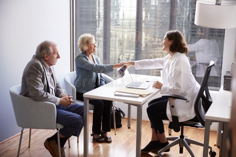Pares mayores que son saludados por visita femenina del doctor With Handshake On al hospital para la consulta fotos de archivo