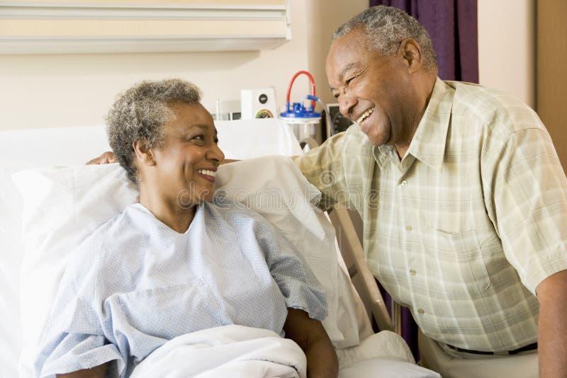 Pares mayores que sonríen en uno a en hospital imagen de archivo libre de regalías