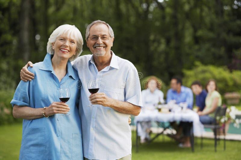 Pares mayores que sostienen las copas de vino en patio trasero imagenes de archivo
