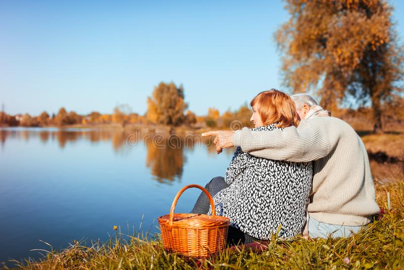 Pares mayores que tienen comida campestre por el lago del otoño Hombre feliz y mujer que disfrutan de la naturaleza y del abrazo foto de archivo libre de regalías