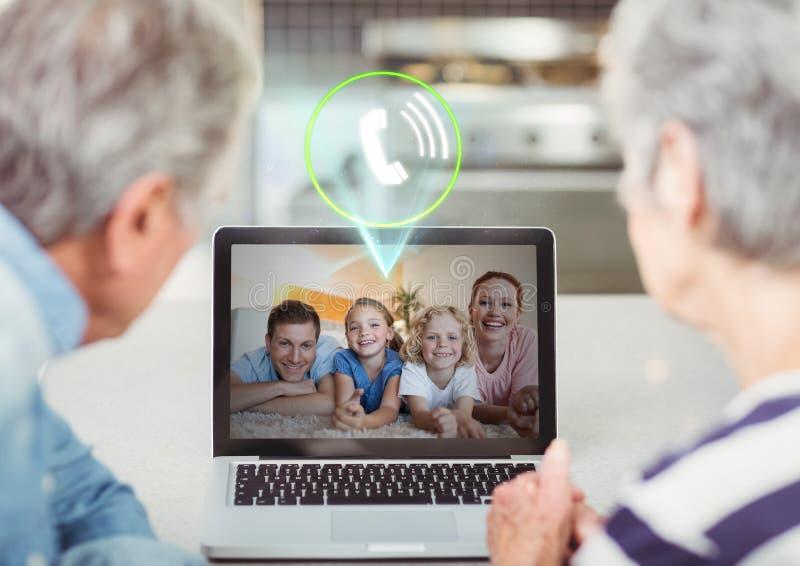 Pares mayores que tienen llamada video con la familia en el ordenador portátil foto de archivo