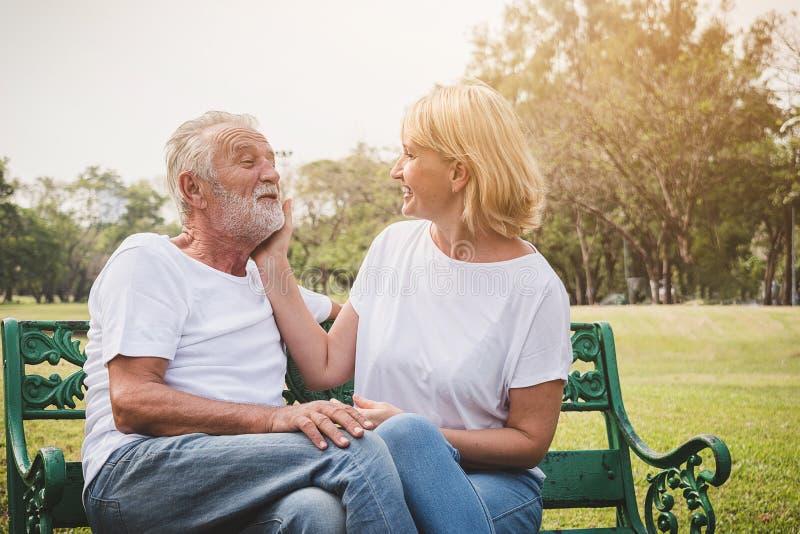 Pares mayores que toman el pelo y que tienen romántico y relajar tiempo en un parque foto de archivo libre de regalías