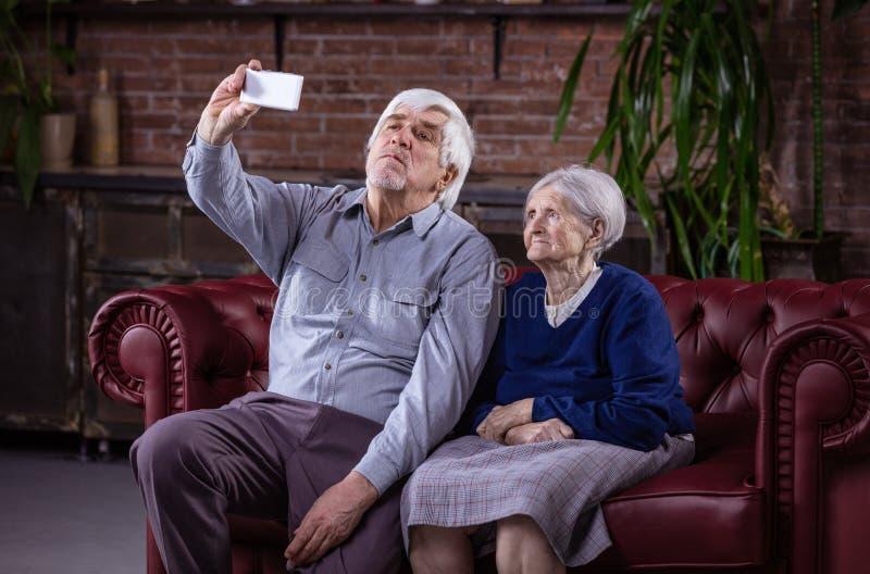 Pares mayores que toman el selfie con el teléfono elegante fotografía de archivo libre de regalías