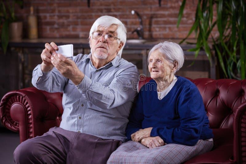 Pares mayores que toman el selfie en el teléfono elegante mientras que se sienta en couc fotos de archivo