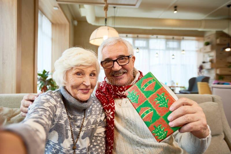 Pares mayores que toman Selfie en la Navidad fotos de archivo