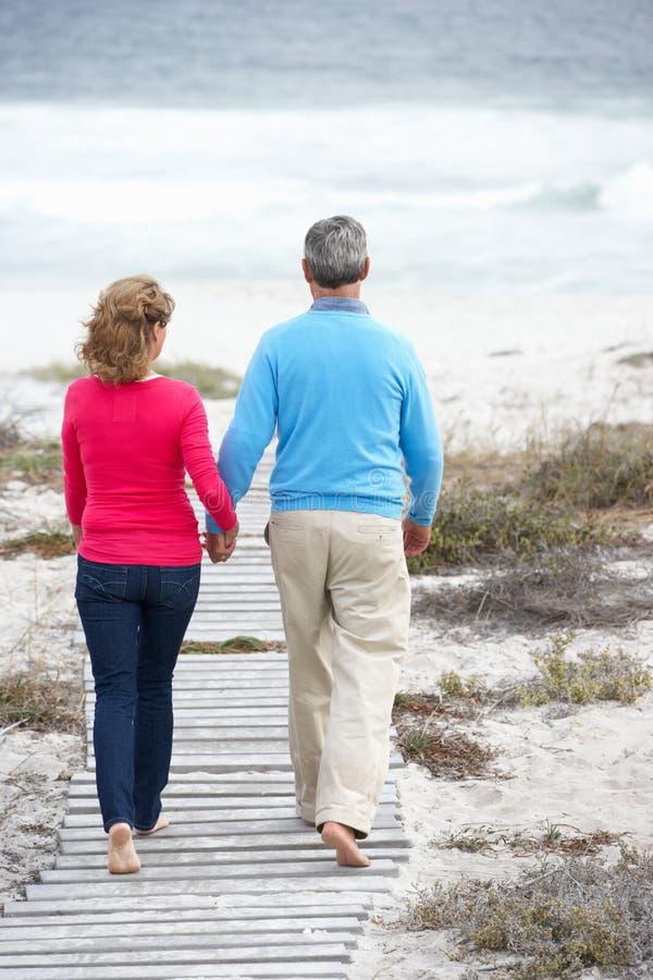 Pares mayores que van para la caminata romántica por el mar imagen de archivo