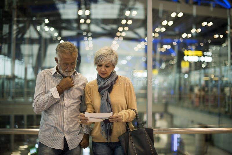 Pares mayores que viajan junto en la escena del aeropuerto fotografía de archivo libre de regalías