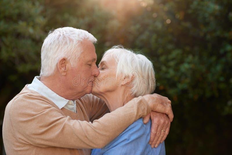 Pares mayores románticos que abrazan y que se besan afuera imagenes de archivo