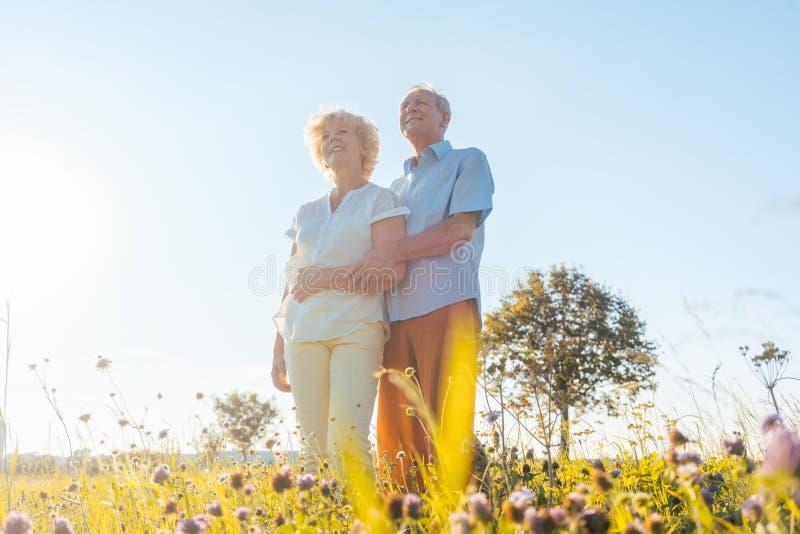 Pares mayores románticos que disfrutan de salud y de la naturaleza en DA soleada foto de archivo