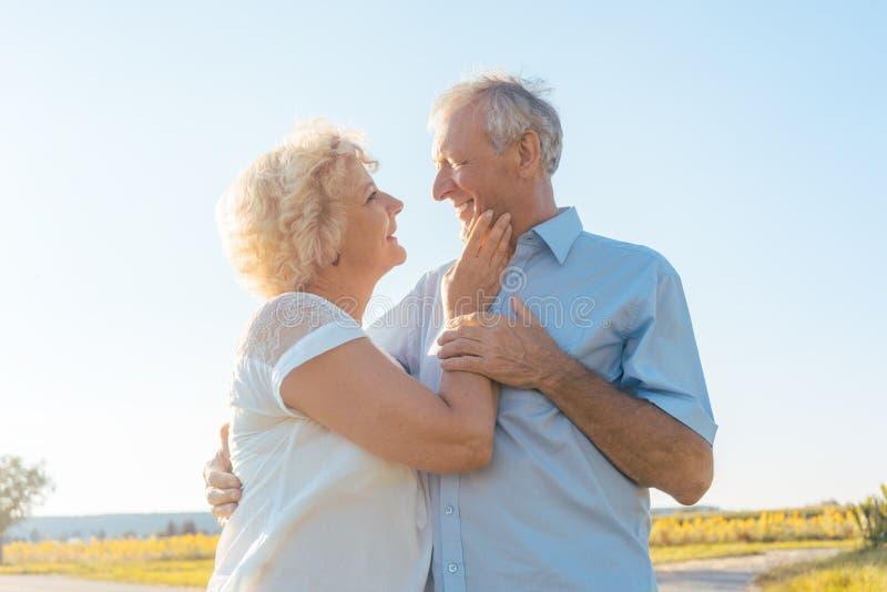 Pares mayores románticos que disfrutan de salud y de la naturaleza en un día soleado foto de archivo