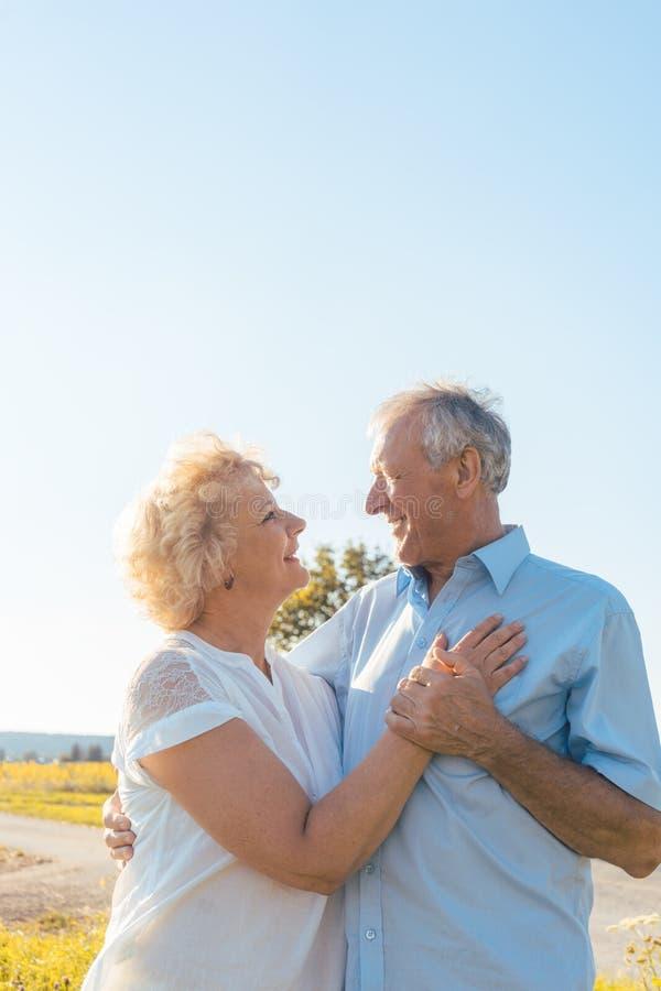 Pares mayores románticos que disfrutan de salud y de la naturaleza en un día soleado fotos de archivo