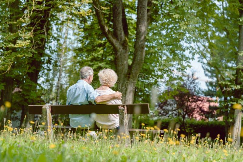 Pares mayores románticos que se sientan junto en un banco en un día de verano tranquilo imagen de archivo