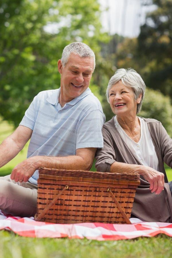 Pares mayores sonrientes con la cesta de la comida campestre en el parque imagen de archivo