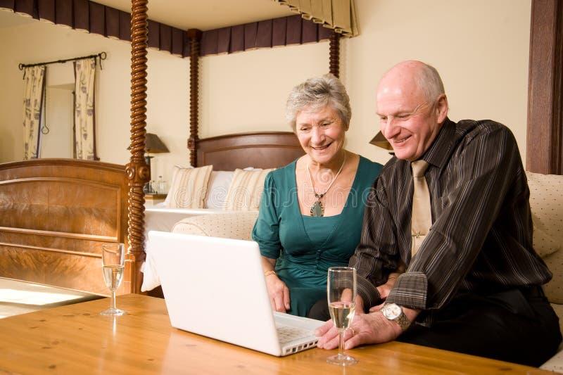 Pares mayores sonrientes con la computadora portátil imagenes de archivo