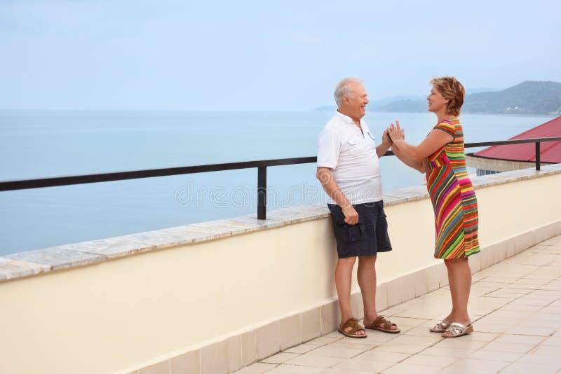 Pares mayores sonrientes en el mirador cerca de la costa foto de archivo libre de regalías
