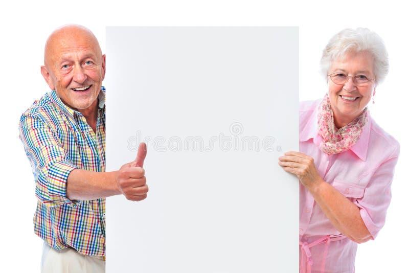 Pares mayores sonrientes felices con una tarjeta en blanco fotografía de archivo libre de regalías