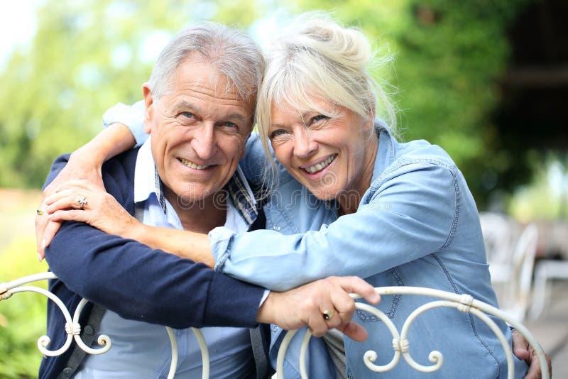 Pares mayores sonrientes felices en el jardín imagen de archivo