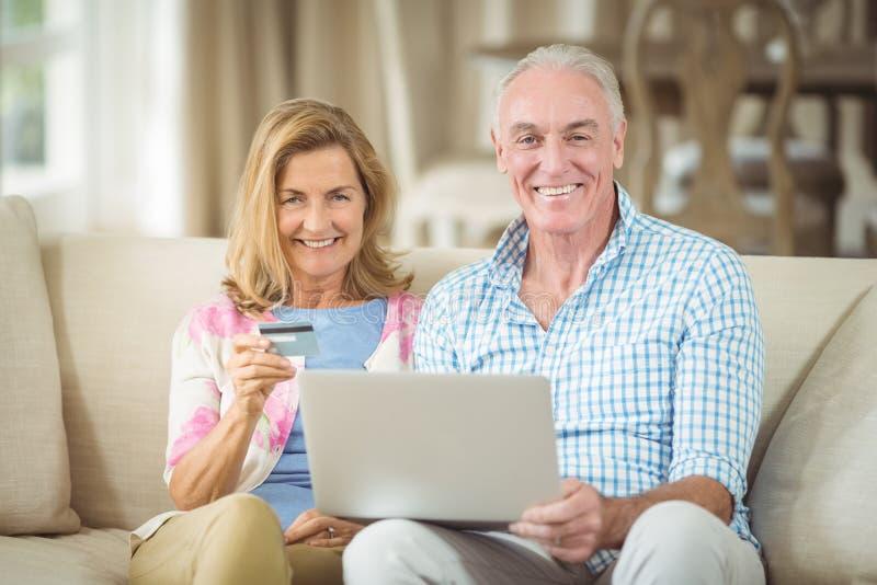 Pares mayores sonrientes que hacen compras en línea en el ordenador portátil en sala de estar fotos de archivo