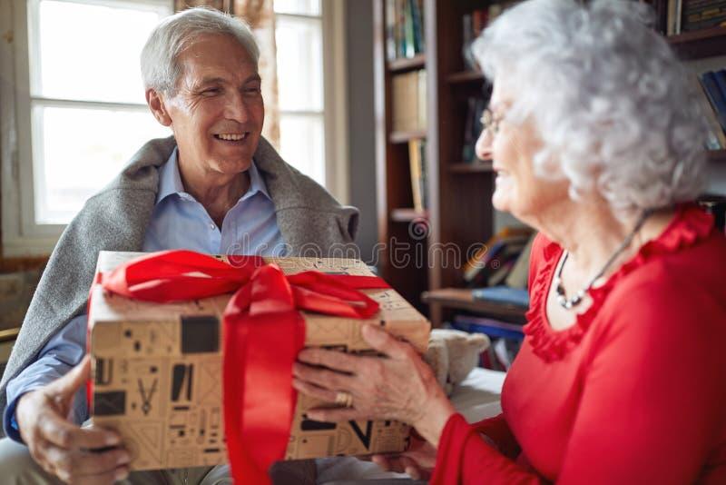 Pares mayores sonrientes que intercambian los regalos de la Navidad fotos de archivo libres de regalías