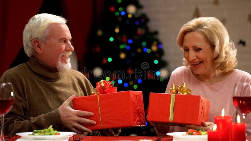Pares mayores sonrientes que llevan a cabo los regalos de Navidad, atmósfera romántica, día de fiesta imagen de archivo libre de regalías