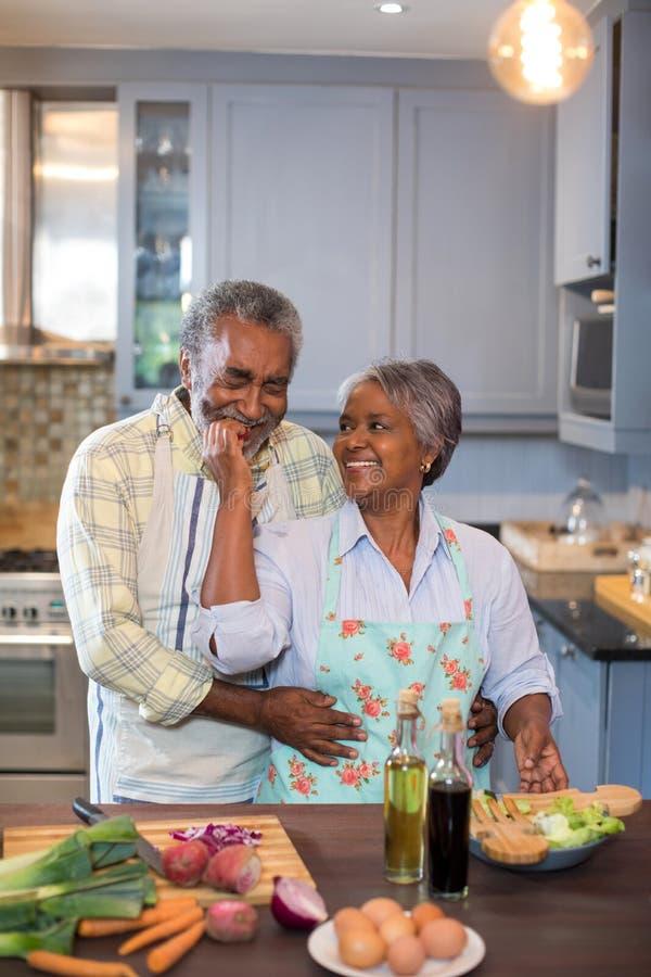 Pares mayores sonrientes que preparan la comida foto de archivo libre de regalías