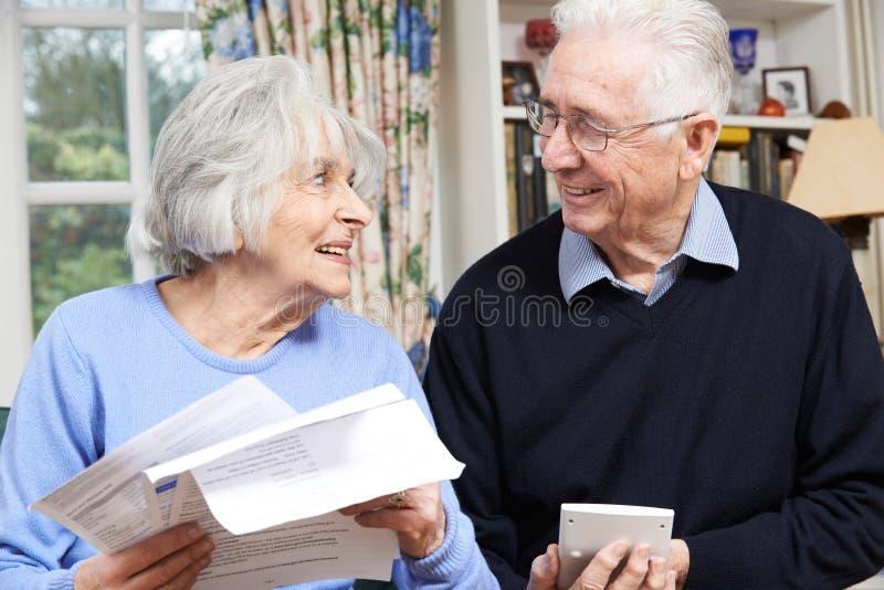 Pares mayores sonrientes que revisan a casa finanzas foto de archivo