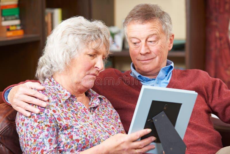 Pares mayores tristes que miran la fotografía en marco junto foto de archivo libre de regalías