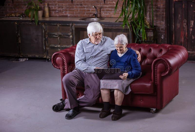 Pares mayores usando el ordenador portátil mientras que se sienta en el sofá fotos de archivo