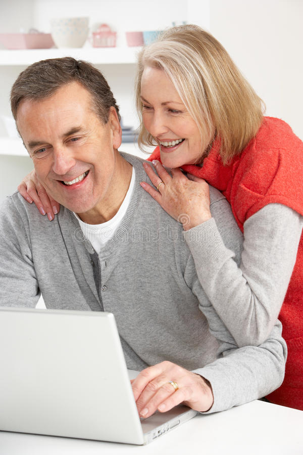 Pares mayores usando la computadora portátil en el país imagen de archivo