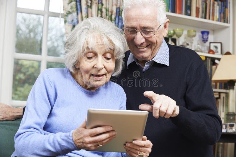 Pares mayores usando la tableta de Digitaces en casa imagenes de archivo