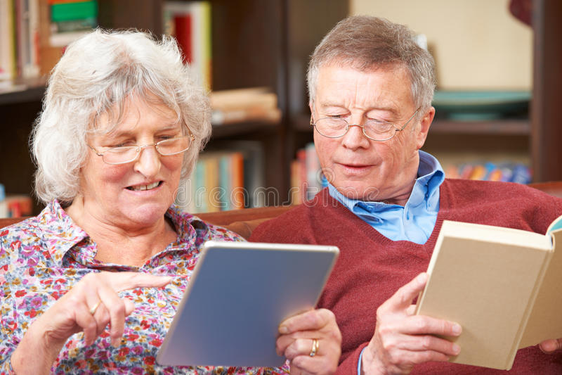 Pares mayores usando la tableta de Digitaces y el libro de lectura imagen de archivo libre de regalías