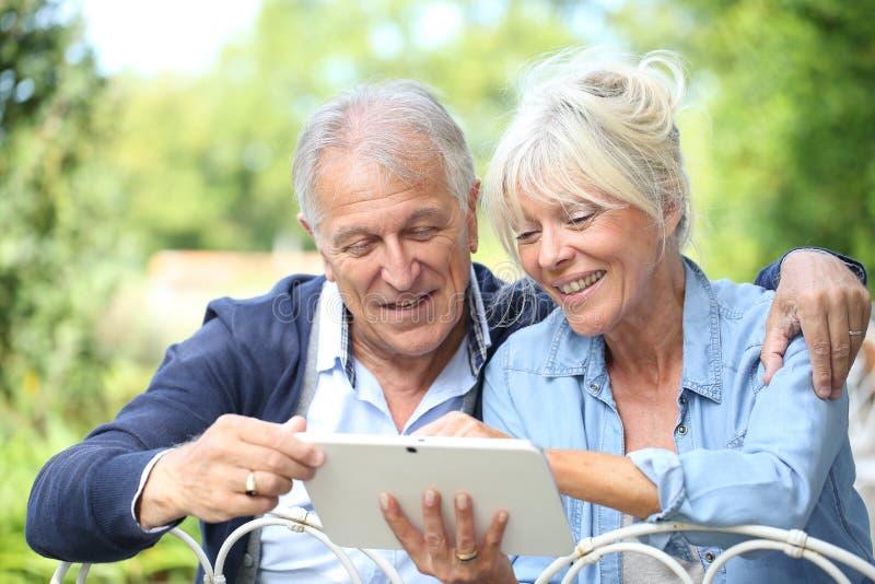 Pares mayores usando la tableta y la sonrisa fotografía de archivo